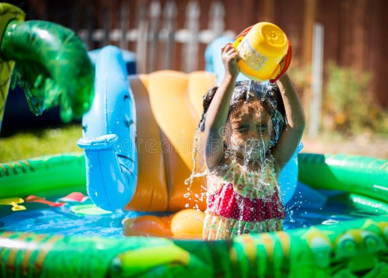 飞溅在水池的女婴与一个桶水 免版税库存图片