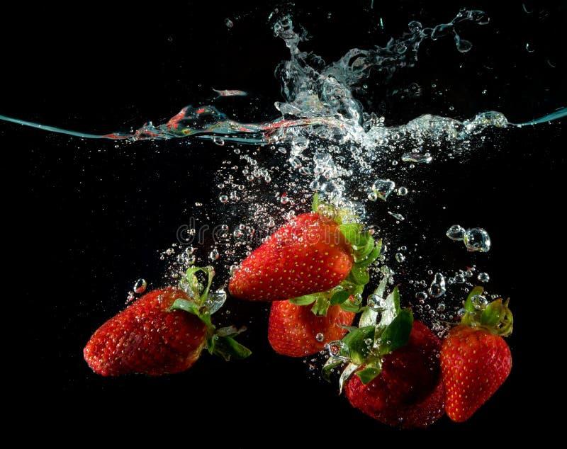 飞溅新鲜的草莓浇灌在黑色 图库摄影