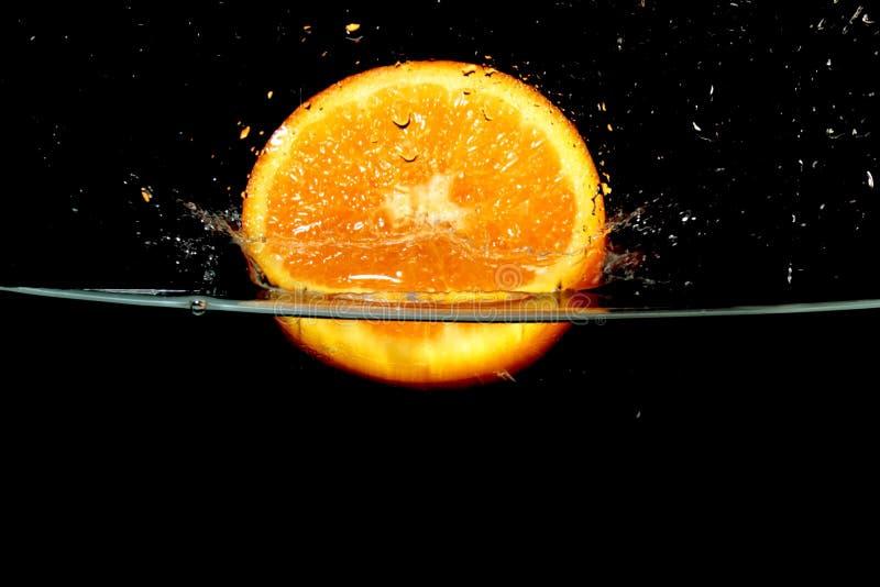 飞溅橙色果子到水里 免版税库存图片