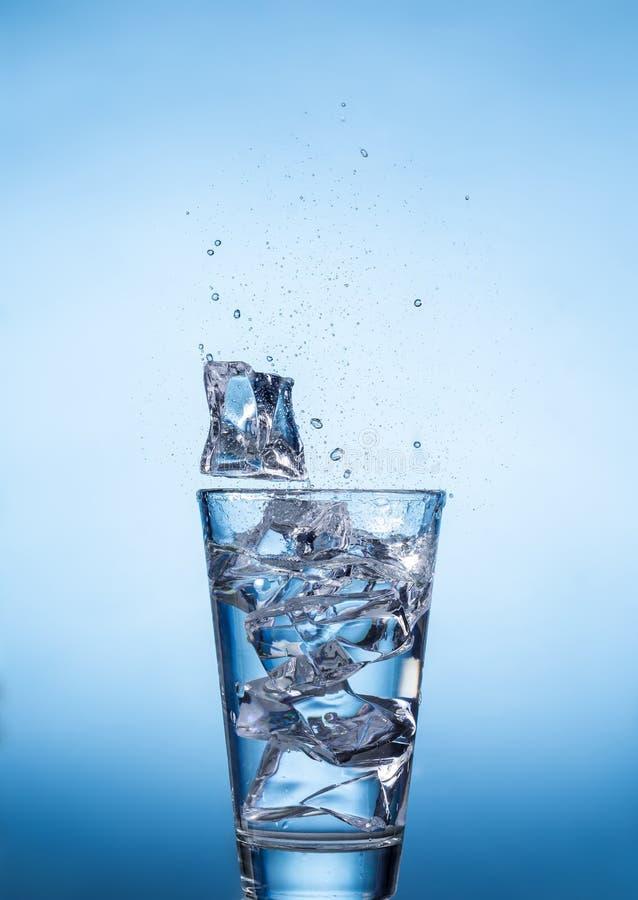 飞溅水水杯与冰块在蓝色背景 免版税库存图片