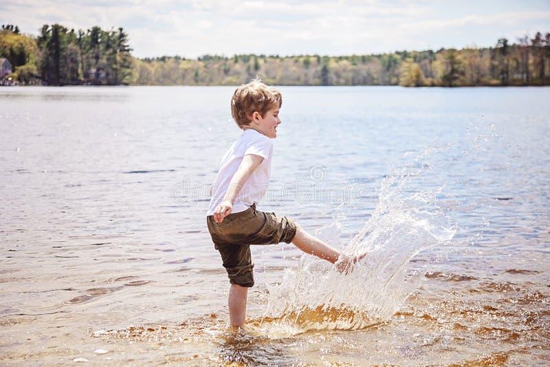 飞溅水的男孩在湖 库存照片