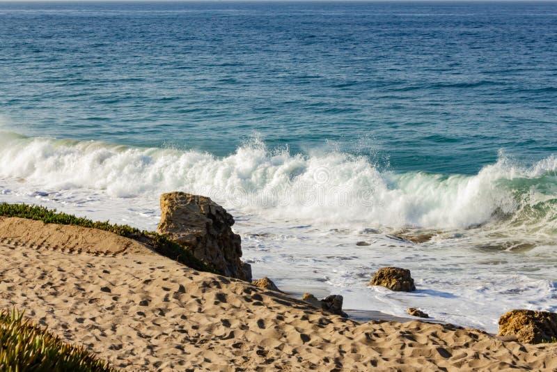 飞溅波浪在回流和沙滩,与大冰砾,沙子 库存图片