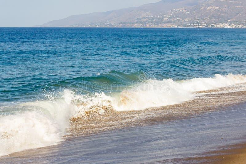 飞溅波浪,跟随由胀大的波浪在海洋浩瀚,在一个沙滩的起泡沫的回流 免版税库存图片
