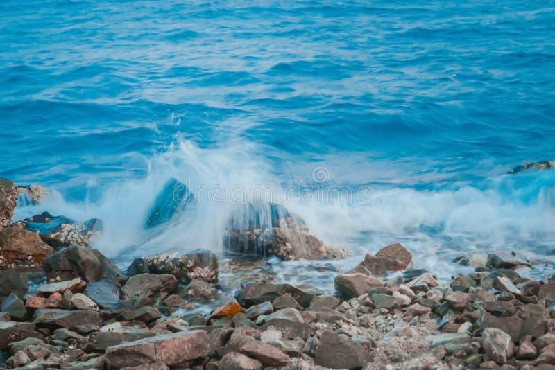 飞溅海水在岩石与蓝色海背景软的fo 免版税库存照片