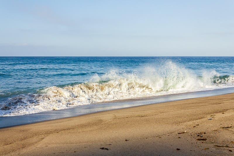 飞溅碎波在含沙岸与回流和天际 免版税库存照片