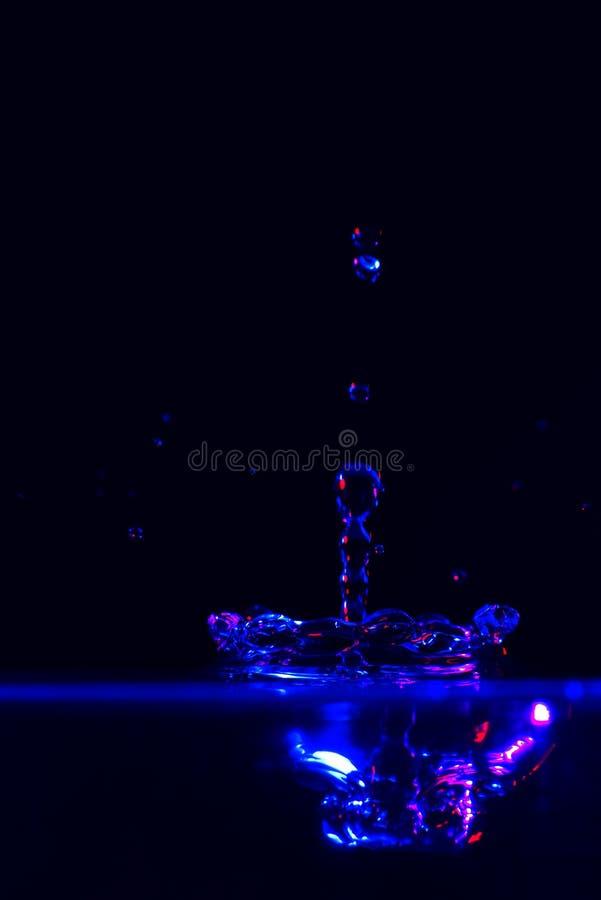 飞溅色的水在黑背景 免版税图库摄影