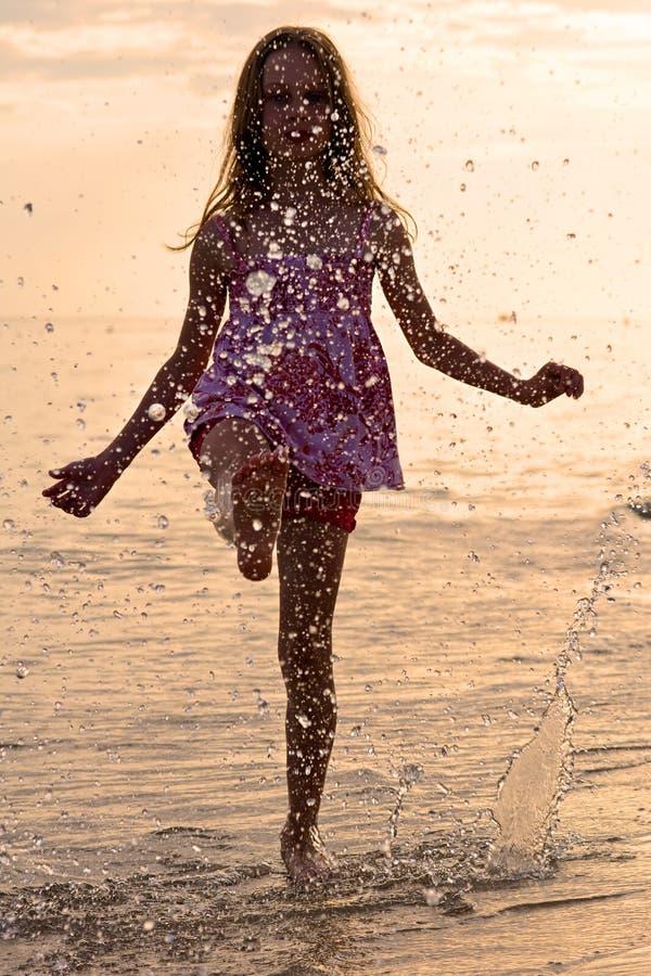 飞溅水的愉快的女孩在暑假期间 免版税库存照片