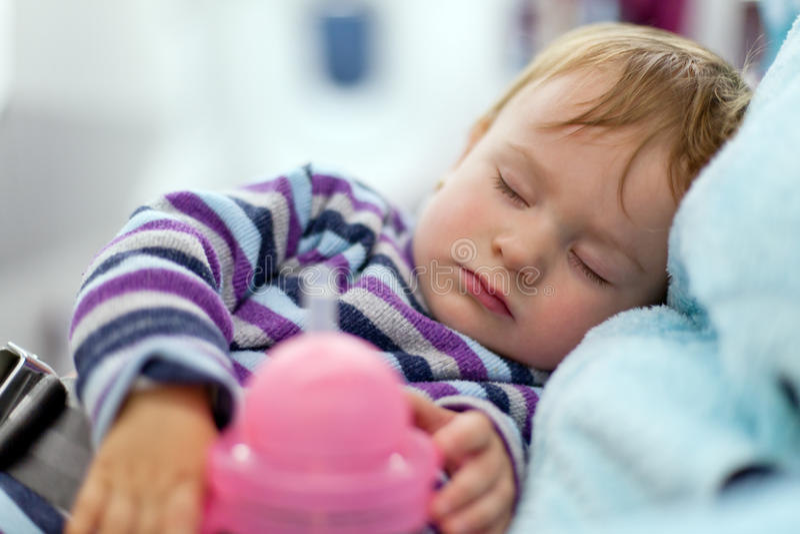 照顾和在飞机的睡觉两岁的女婴旅行 图库摄影
