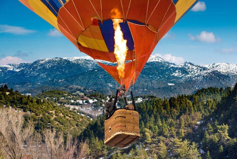 飞行从Mainalo的乘客到热空气气球篮子里和火焰到Helmos山 世外桃源,希腊 免版税库存图片