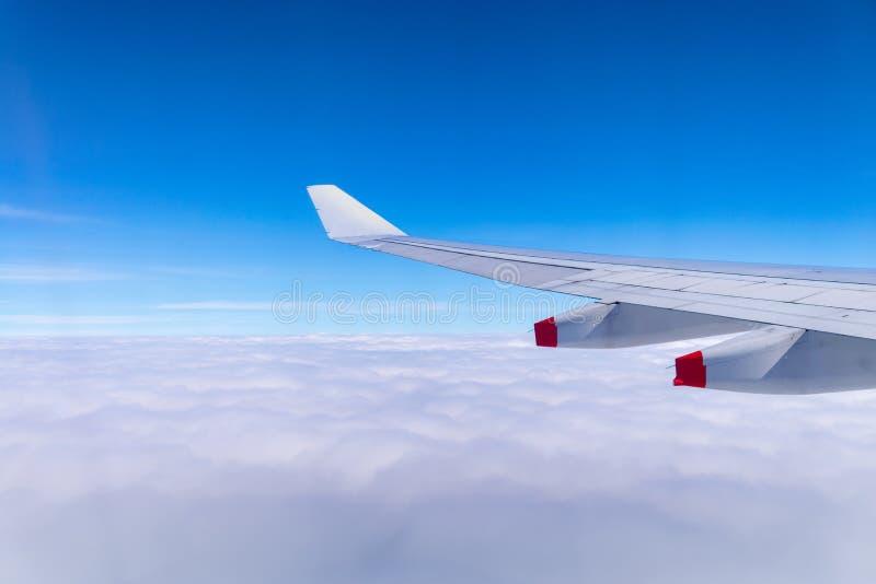 飞行入飞机云彩和翼蓝天和海与 免版税库存图片