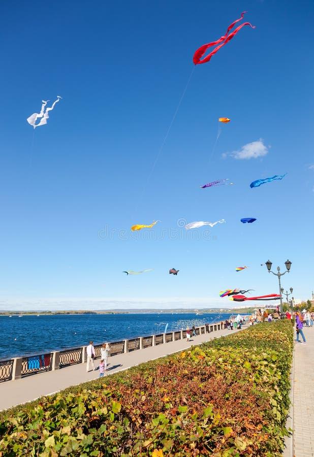 飞行反对在城市堤防的蓝天的五颜六色的风筝 库存图片