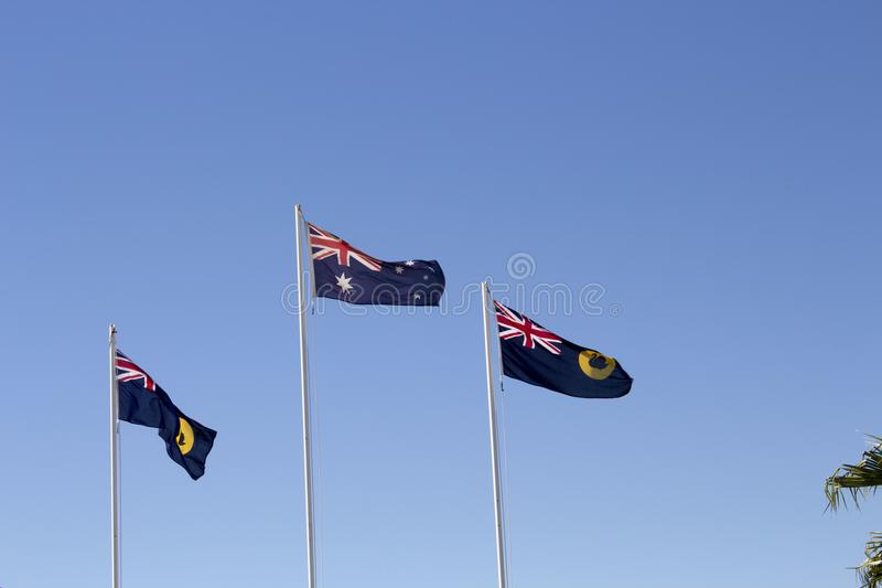 飞行反对蓝天的澳大利亚和西部澳大利亚旗子 免版税库存图片