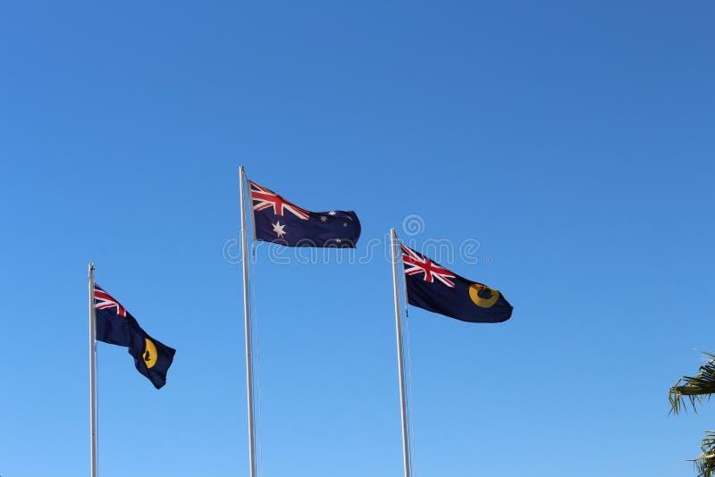 飞行反对蓝天的澳大利亚和西部澳大利亚旗子 免版税库存照片
