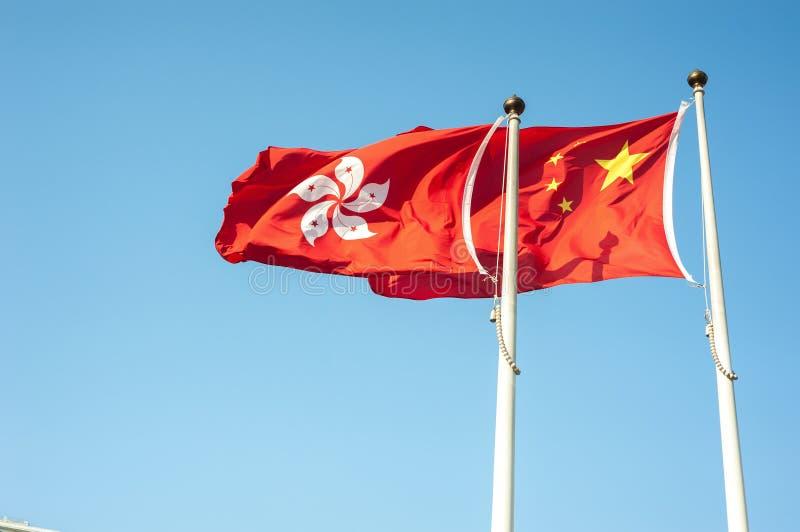 飞行反对蓝天的香港和中国旗子 库存图片