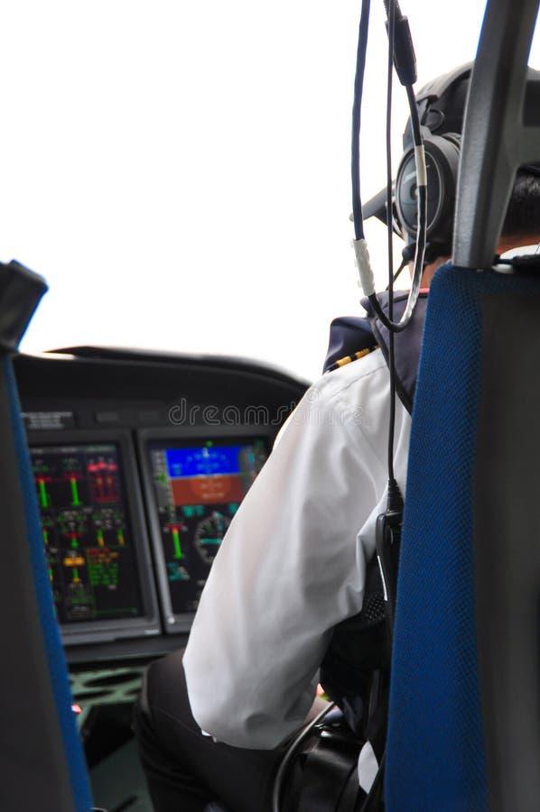 飞行员和副驾驶公司飞机的在驾驶舱内,引导操作与控制板 免版税库存图片