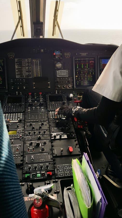 飞行员和副驾驶公司飞机的在驾驶舱内,引导操作与控制板 库存图片