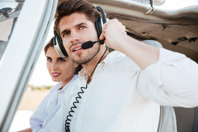 年轻飞行员和美丽的空中小姐画象在飞机客舱里面 库存照片