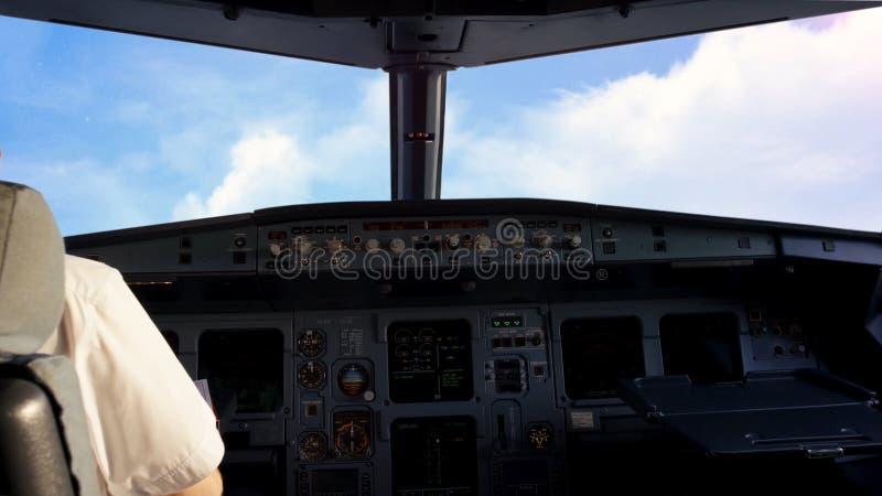 飞行员在一架小商用飞机的驾驶舱内在一个农村风景上的,多云天空背景 的飞行员 免版税库存图片