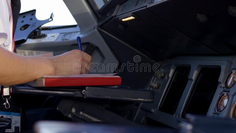 飞行员在平面驾驶舱内的检查仪器 公司喷气机飞行员运行的控制背面图  飞行员 库存照片