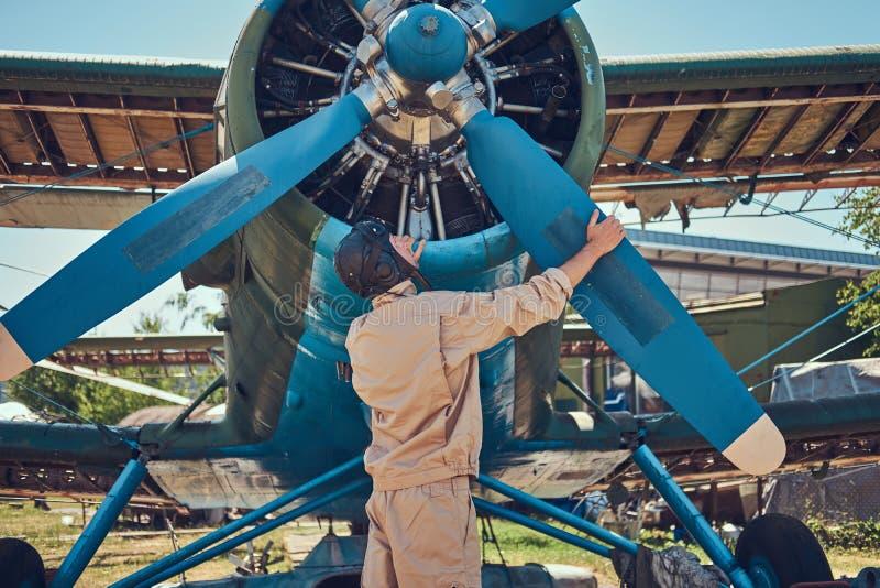 飞行员或技工一个充分的飞行齿轮的在飞行前检查他减速火箭的军用飞机推进器  库存照片