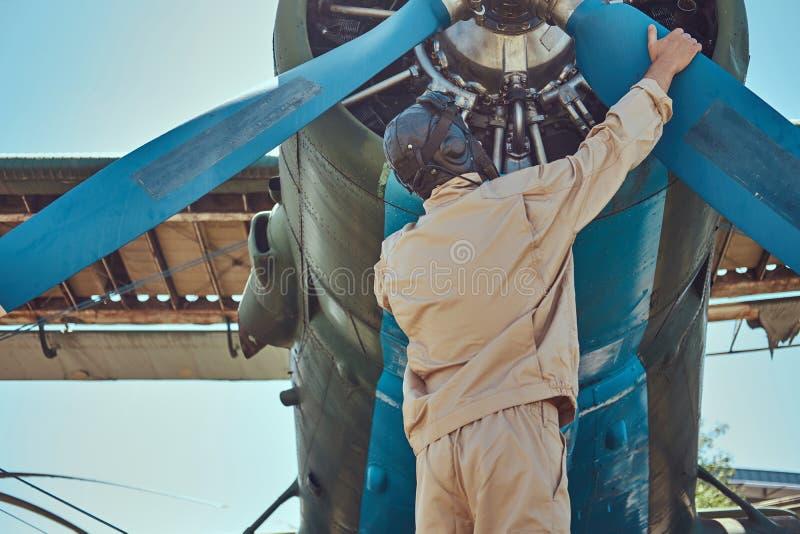 飞行员或技工一个充分的飞行齿轮的在飞行前检查他减速火箭的军用飞机推进器  库存图片