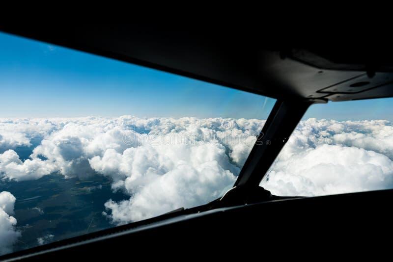 飞行员观看在驾驶舱窗口外面往上面云彩和天空蔚蓝 图库摄影