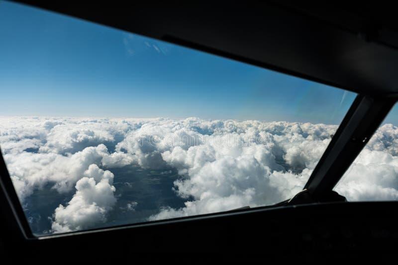 飞行员观看在驾驶舱窗口外面往上面云彩和天空蔚蓝 库存图片