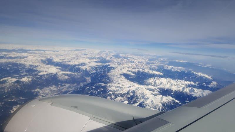 飞行和旅行海外,从飞机窗口的俯视图在多云天空蔚蓝冰山山的喷气机翼早晨 免版税库存照片