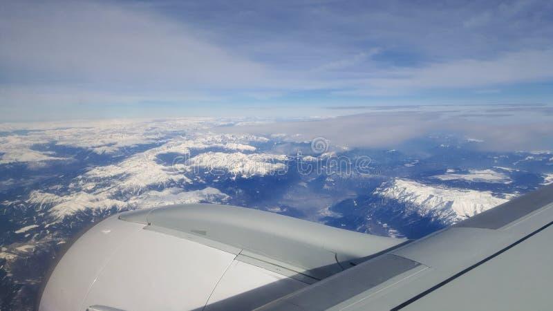 飞行和旅行海外,从飞机窗口的俯视图在多云天空蔚蓝冰山山的喷气机翼早晨 免版税图库摄影