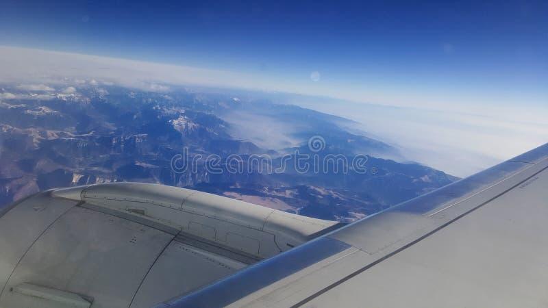 飞行和旅行海外,从飞机窗口的俯视图在多云天空蔚蓝冰山山的喷气机翼早晨 免版税库存图片