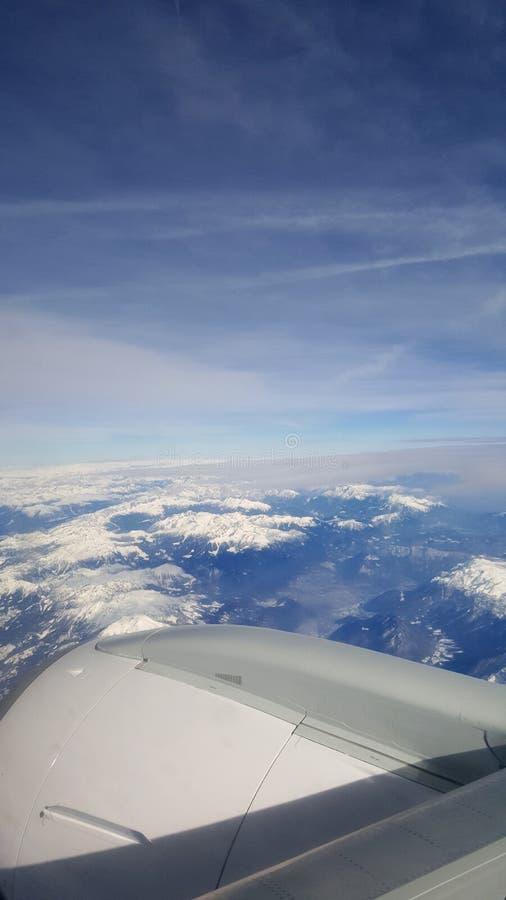 飞行和旅行海外,从飞机窗口的俯视图在多云天空蔚蓝冰山山的喷气机翼早晨 库存照片