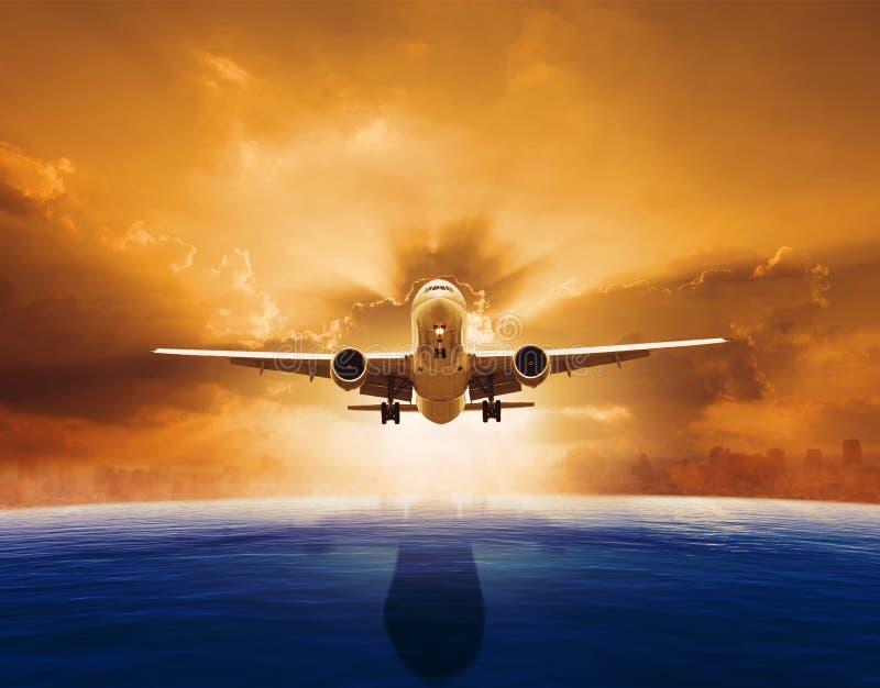 飞行在与太阳集合的美好的海平面的喷气式客机飞机 免版税图库摄影