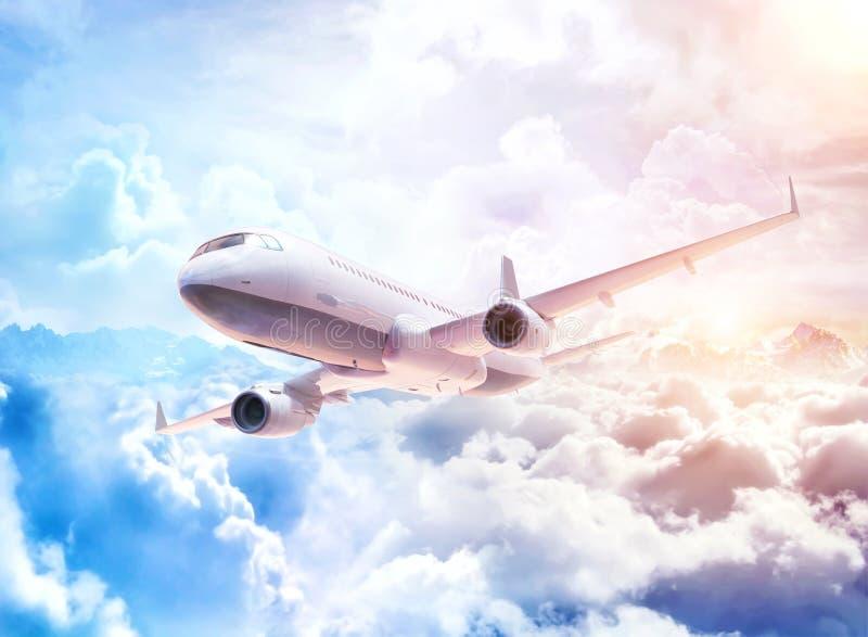 飞行在云彩的白色商业飞机在与云彩和山峰的意想不到的背景 皇族释放例证