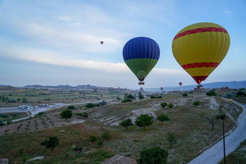 飞行在卡帕多细亚独特的风景上的五颜六色的气球美好的全景研了有蓝天背景在日出 库存照片