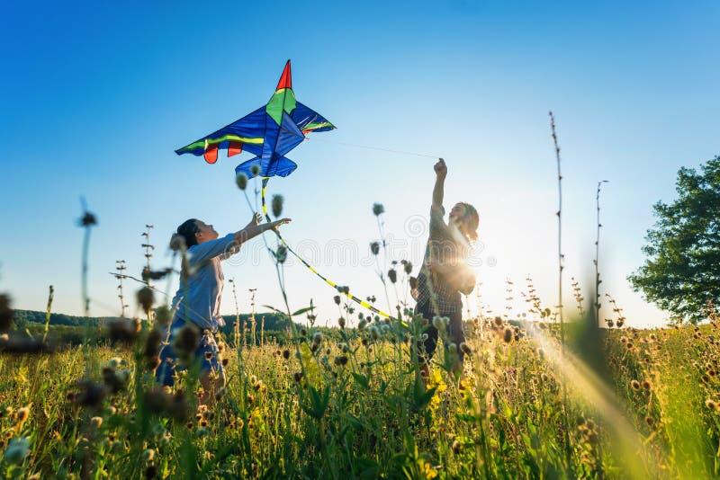 飞行在夏天领域、夏天幸福和爱概念的年轻愉快的美好的夫妇一只风筝 免版税库存照片