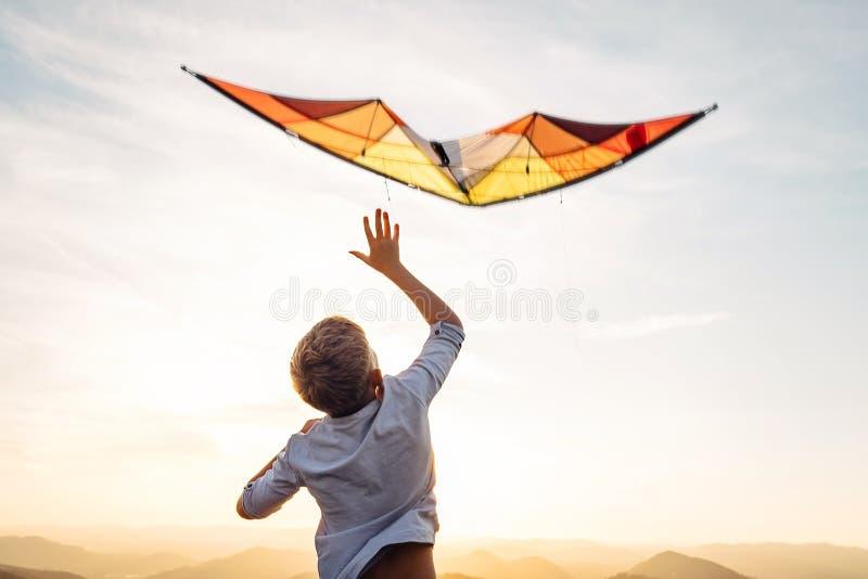 飞行在天空的明亮的橙色风筝的男孩开始 免版税图库摄影