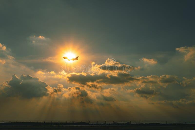 飞行在天空的民航飞机反对美丽的太阳光芒throu 库存图片
