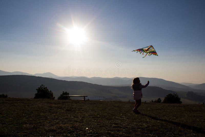 飞行在山兹拉蒂博尔,塞尔维亚小山的愉快的女孩一只风筝  免版税库存照片