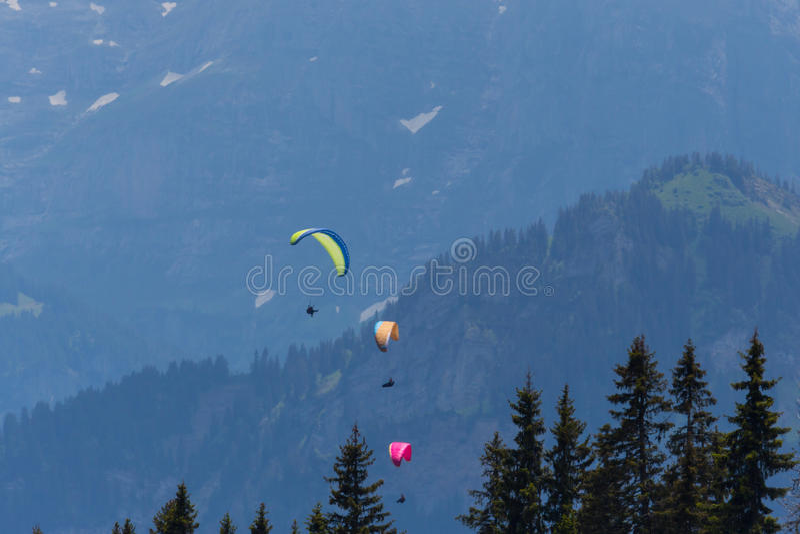飞行在山的三个滑翔伞 免版税库存图片