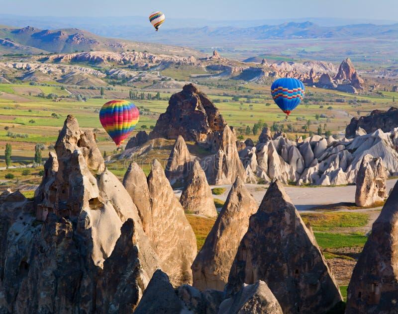 飞行在岩石风景的热空气气球在卡帕多细亚,土耳其 免版税库存照片