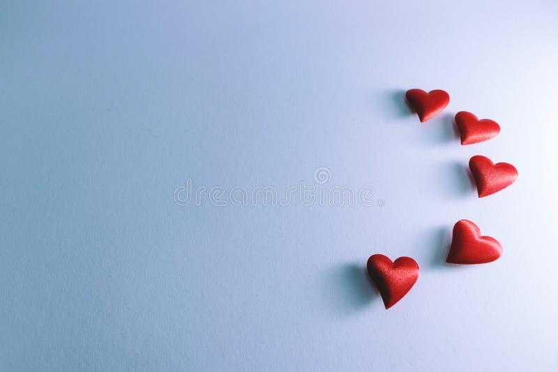 飞行在白色背景的许多一点红色心脏 库存照片