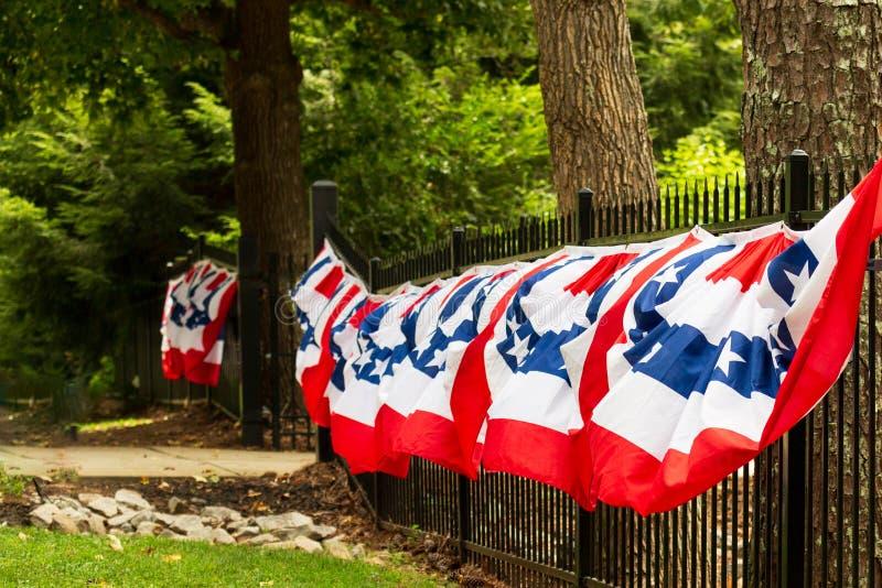 飞行在篱芭的旗子庆祝美国自由和尊敬在军事担任的那些人 免版税库存照片