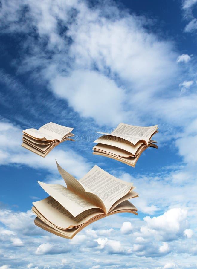 飞行在蓝天的三本开放书 免版税图库摄影