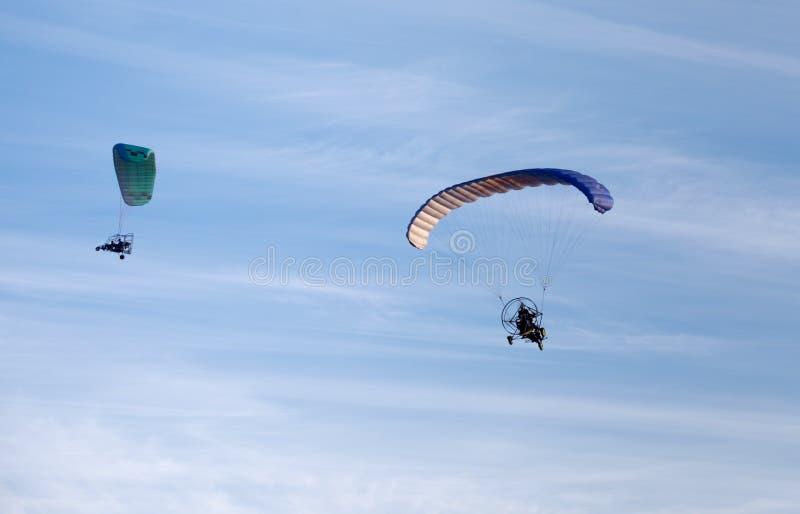 飞行在蓝天的两个动力化的滑翔伞 免版税库存图片