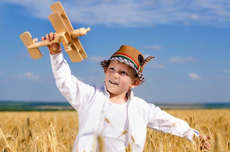 飞行在麦田的小男孩一架玩具飞机 免版税库存照片