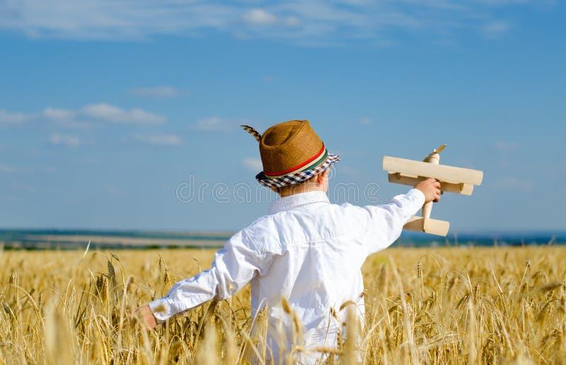 飞行在wheatfield的逗人喜爱的小男孩一架玩具飞机 免版税库存图片