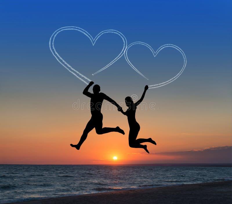 飞行它的爱恋的夫妇天空反对心形海的beachand 免版税图库摄影