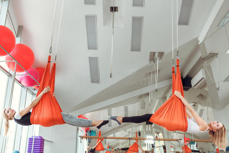 飞行瑜伽 两与吊床的妇女实践反地心引力的瑜伽 库存照片