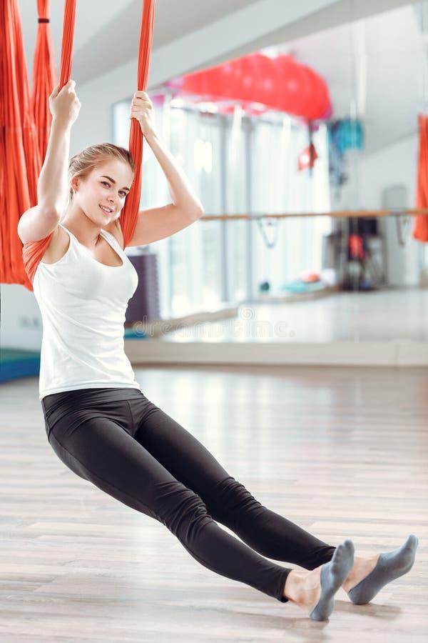 飞行瑜伽 少妇实践与吊床的空中反地心引力的瑜伽 库存图片