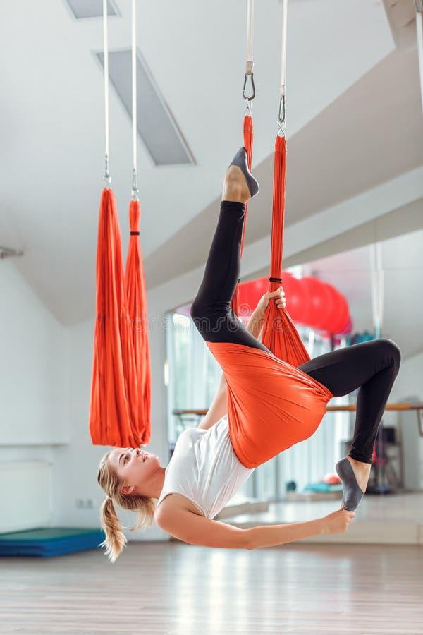 飞行瑜伽 少妇实践与吊床的空中反地心引力的瑜伽 库存照片